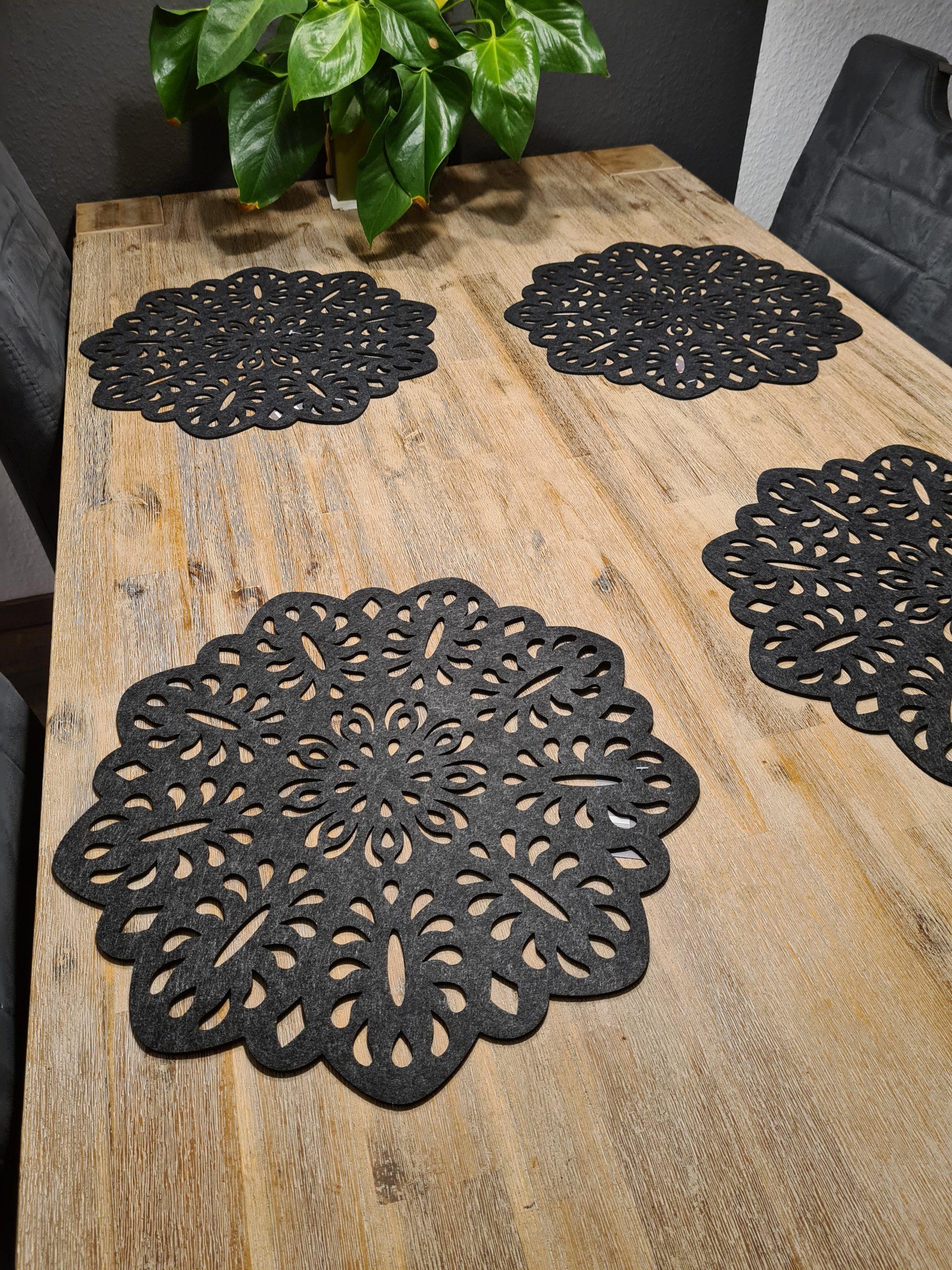 schwarze Filz-Untersetzer mit Ausstanzungen auf Holztisch - Handgemachte individualisierbare Taschen, Körbe, Tischsets, Dekoartikel und mehr auf fideko.de der Onlineshop seit 2011